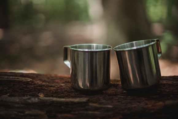 metal mugs on tree trunk in woods