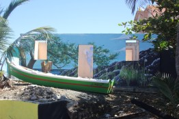 A boat lies outside a dilapidated building painted with murals (Nikita Mandhani/Medill)