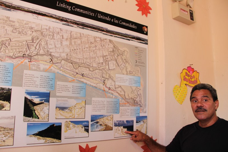 Coco explains proposed development plans for the seaside walkway, posted in the La Perla community center (Kari Lydersen/Medill)