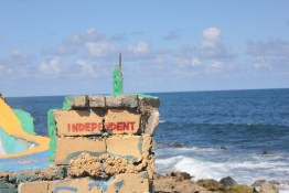 """A ruined wall by the ocean has the word """"independent"""" marked on it (Nikita Mandhani/Medill)"""