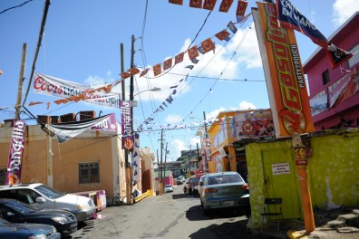 A street in the La Perla neighborhood with rows of cars and colorful fliers (Bill Healy/Medill)