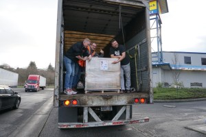 Toilet Paper Drive Brad and John standing in Truck with A pallet of donations