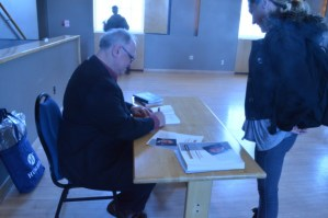 A picture of a man signing a book for a girl.