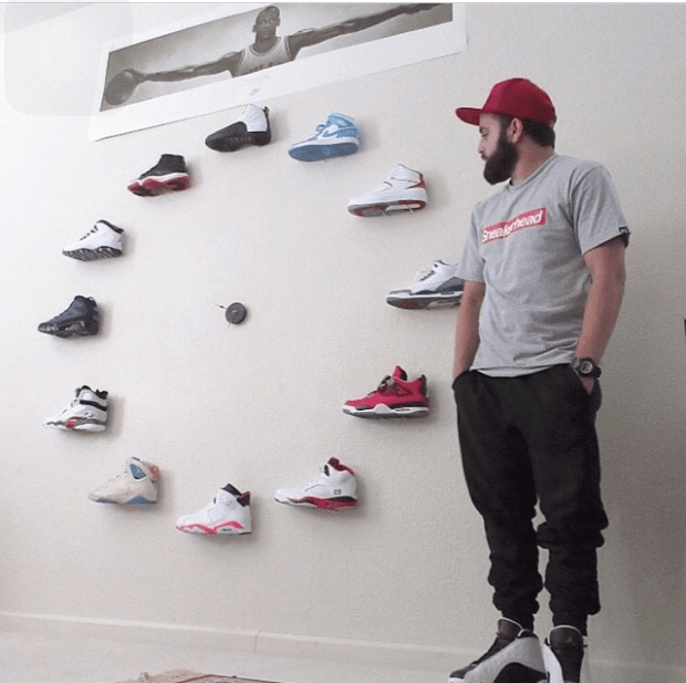A man wearing a red hat with his hands in his pockets looking at a wall display of shoes in the shape of a circle.