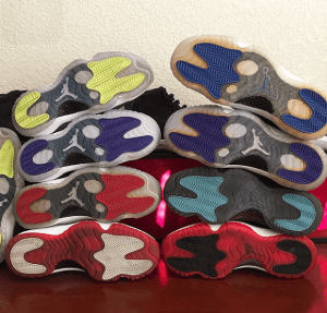 Shoes piled onto of each other with the bottoms facing the camera.