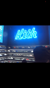 A neon blue light up sign that reads Kith inside a shoe store .