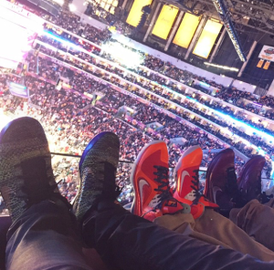 The legs of three people wearing sneakers watching a basketball game inside a stadium/arena.