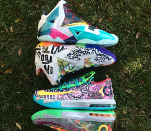 Two pairs of mismatched sneakers placed bottom against bottom on the grass.
