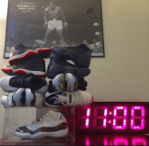 A shoe in a see through display box with shoes piled on top of it. To the right of the box is a digital clock that reads 11:00. In the background hangs a picture of boxer Muhammad Ali in the ring looking down at opponent Sonny Liston.