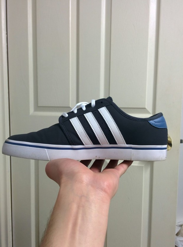 A hand holding a shoe that is black with three white stripes on the side.