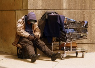 A homeless man on the street with a shopping cart filled with his things.