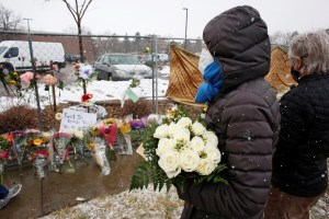 People leave flowers at the site of a mass shooting in Boulder. March 23, 2021.