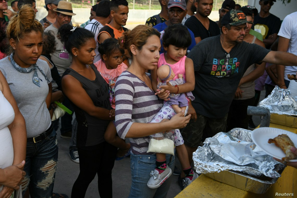 FILE - Asylum-seekers line up for a meal provided by volunteers as they wait in a makeshift migrant camp near the Gateway International Bridge in Matamoros, Tamaulipas, Mexico, June 29, 2019.