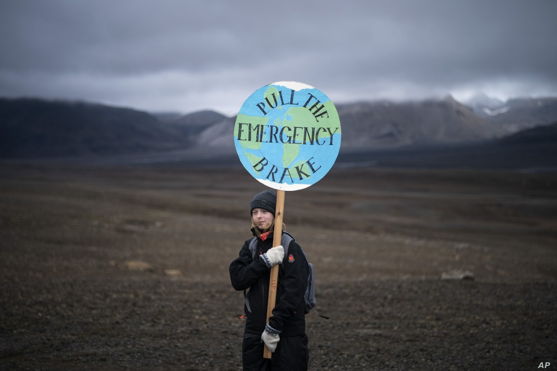 A girl holds a sign that reads 'pull the emergency brake' as she attends a ceremony in the area which once was the Okjokull glacier, in Iceland, Sunday, Aug. 18, 2019.