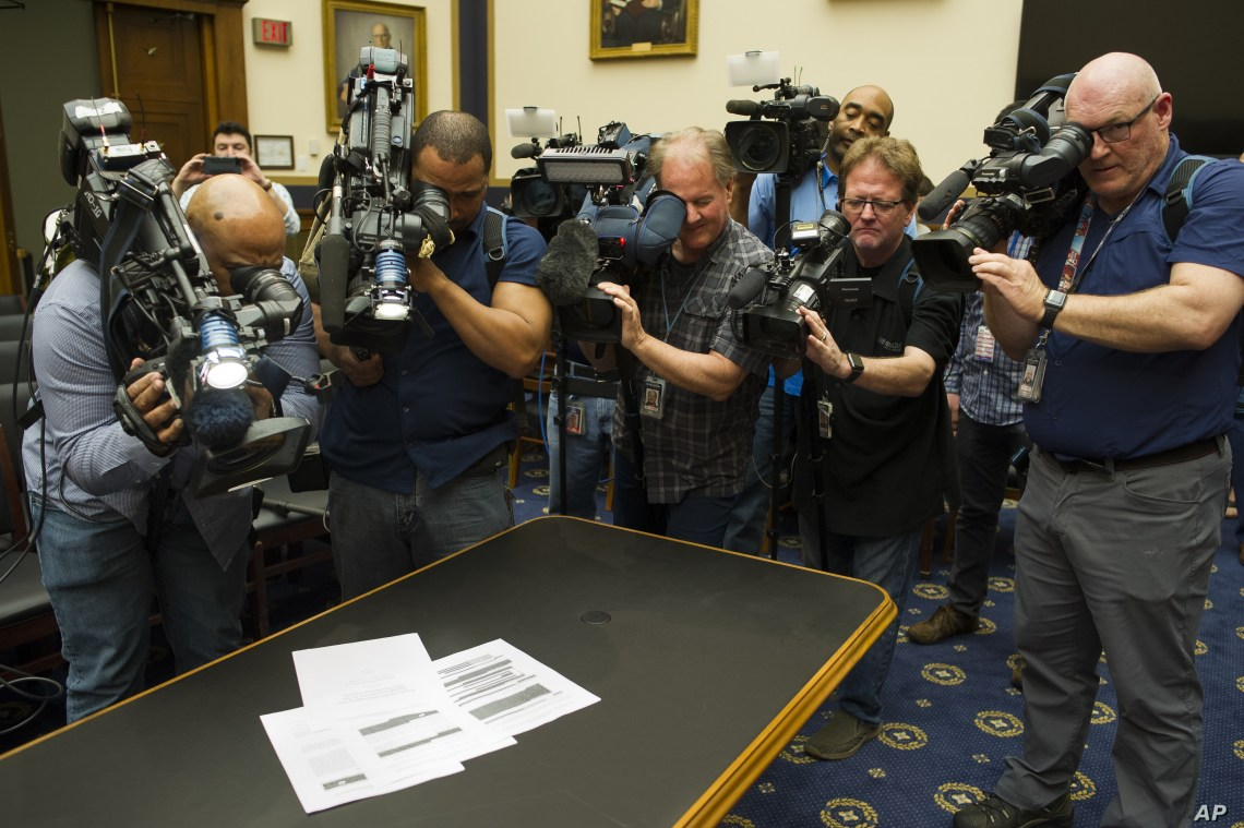 Photojournalists photograph four pages of the Mueller Report laid on the witness table in the House Intelligence Committee hearing room on Capitol Hill, April 18, 2019.