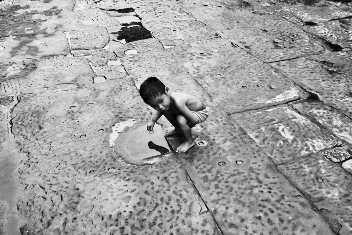 No, he is not peeing! Just curious about his reflection in the wet spot (Angkor Wat, Cambodia)
