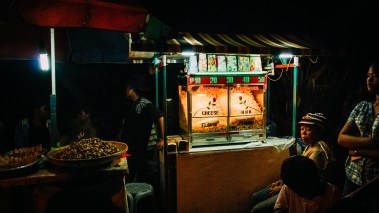 Vendors on a night market waiting for customers to buy their special flavored popcorn. You can choose between cheese and bbq. Since I only new the sweet one back then I needed to get used to that taste... (Dumaguete, Philippines)