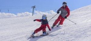 Kind mit Vater beim Skifahren