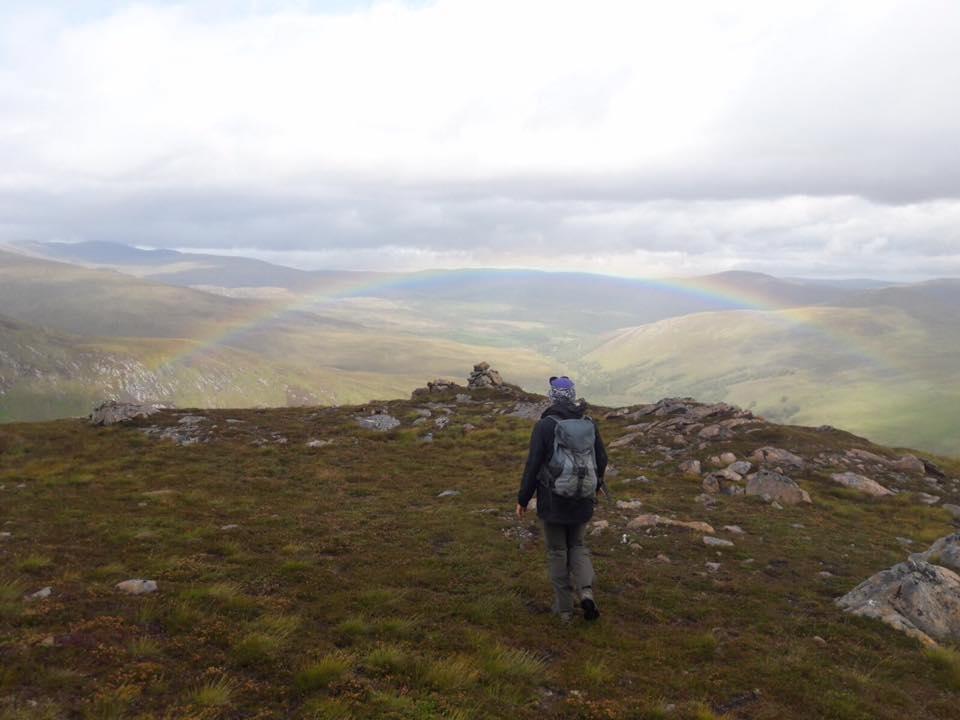 Coach walking towards rainbow.