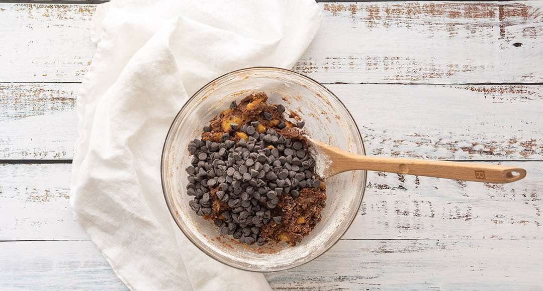 Chocolate chips in a bowl top down view, with wooded spoon