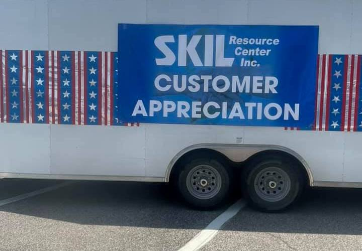 white trailer with blue banner with white lettering reading SKIL Resource Center Inc. CUSTOMER APPRECIATION