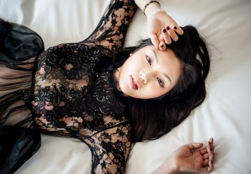 girl lays in bed in black dress staring up at camera