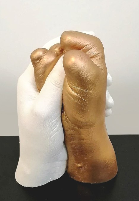 A sculpture of two hands grasping each other, one with fingers, one without.