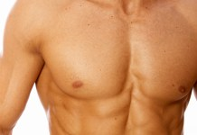 A close up of a man's pecks and six pack abs