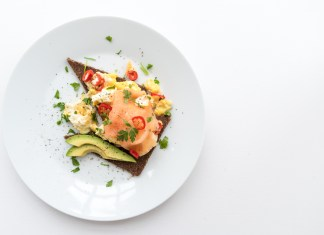 scrambled eggs with smoked salmon and avocado on rye bread recipe served on white plate