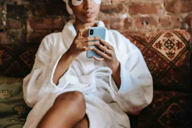 crop ethnic woman text messaging on smartphone at home