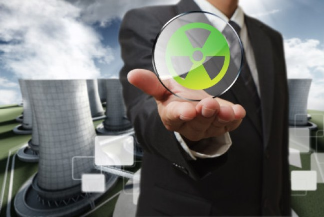 business man hand shows nuclear sign and nuclear power plant background