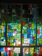 Winter season in stained glass along the chapel wall.