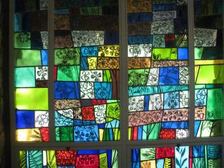 Spring season in stained glass along the wall of the chapel.