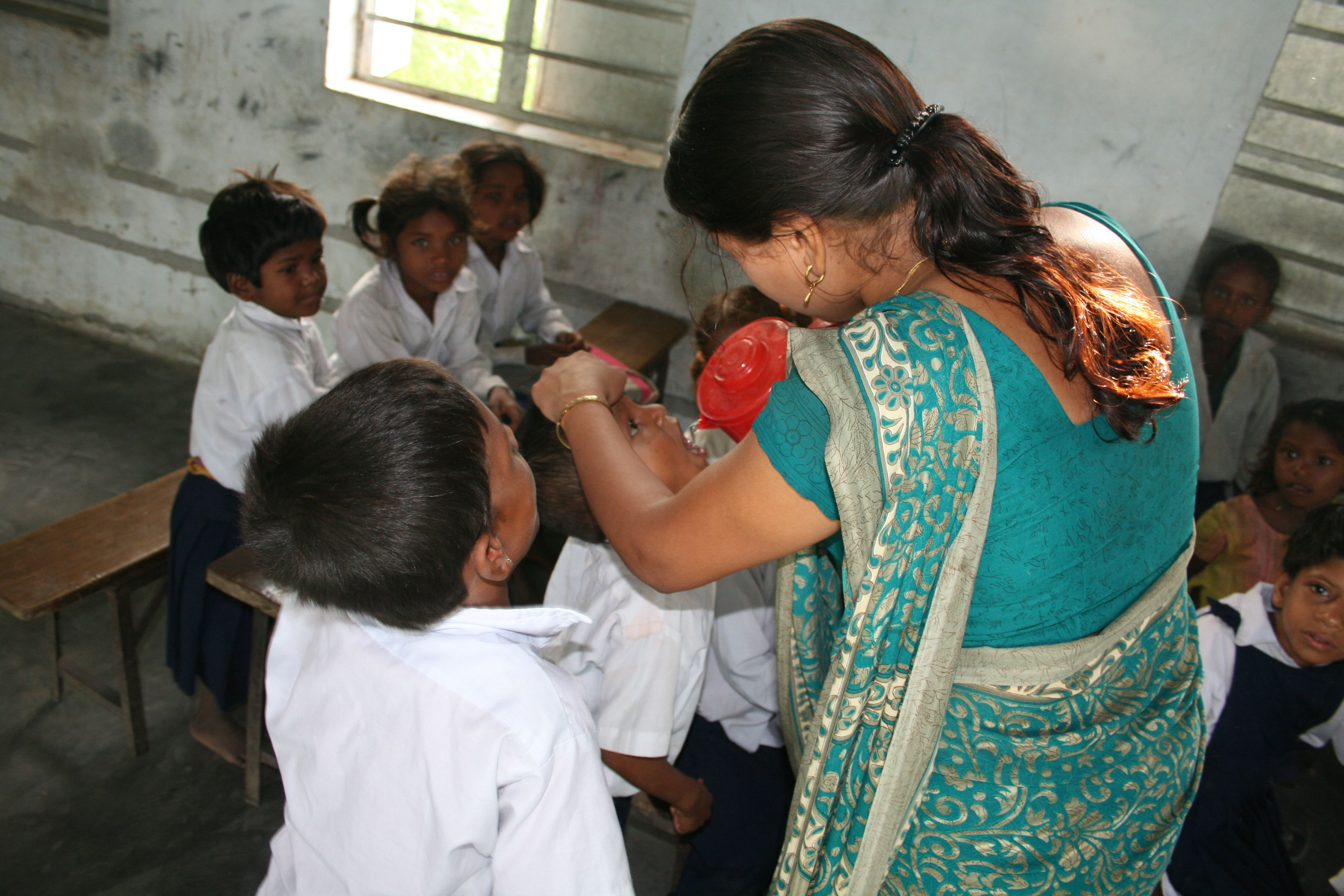 Børnene får vand af deres lærer ms. Menuka