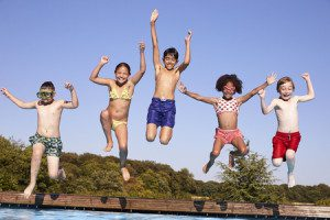 71213509 - group of children jumping into outdoor swimming pool