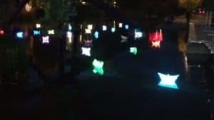 Plastik-Papierschiffchen mit bunten Lampen im Piano-See