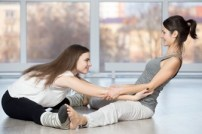 woman-helping-another-stretch-back_1163-996