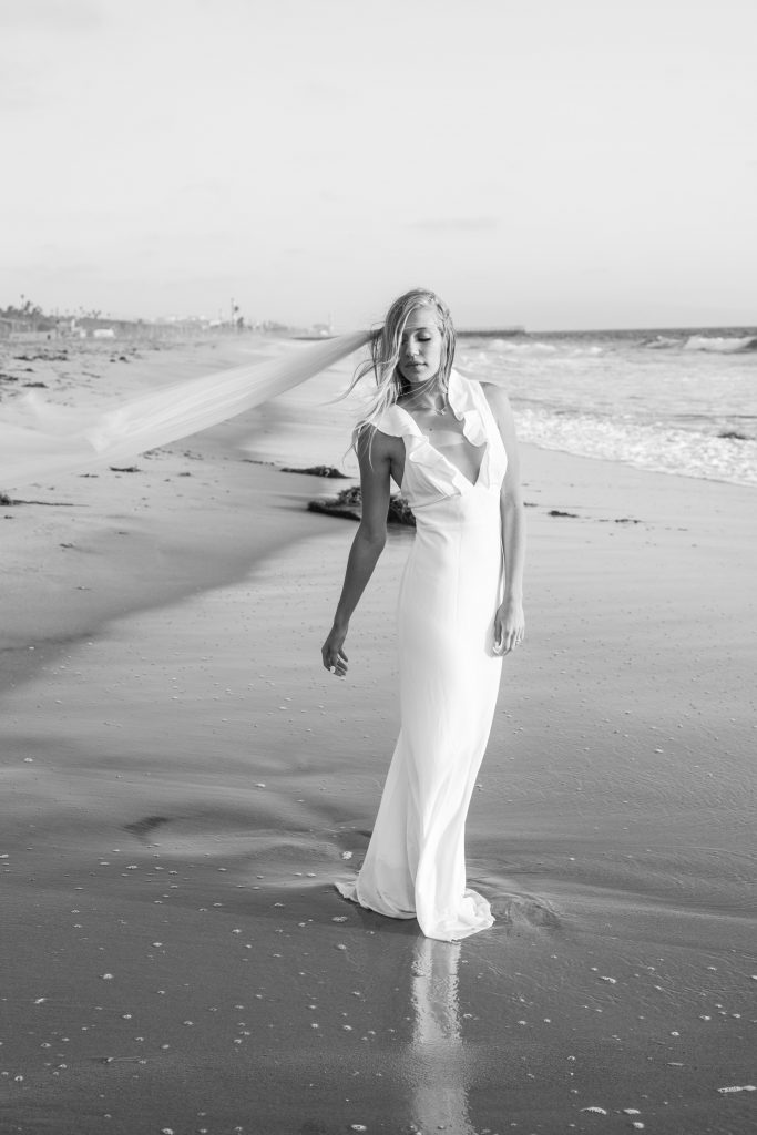 beach wedding bride hops in ocean and gets wet with dress and veil