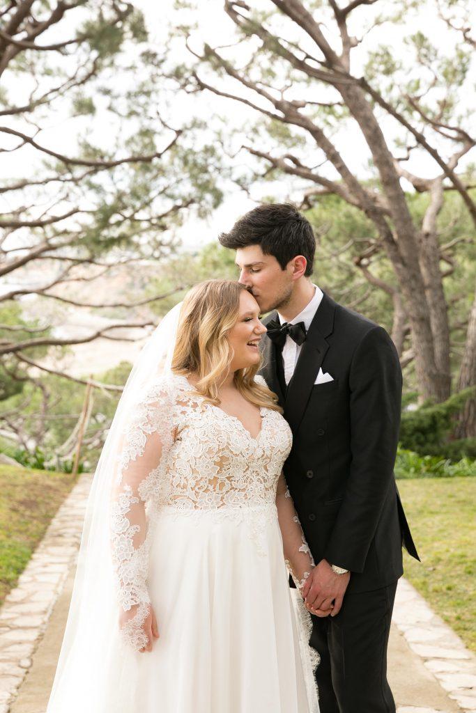 groom kisses bride trees in background