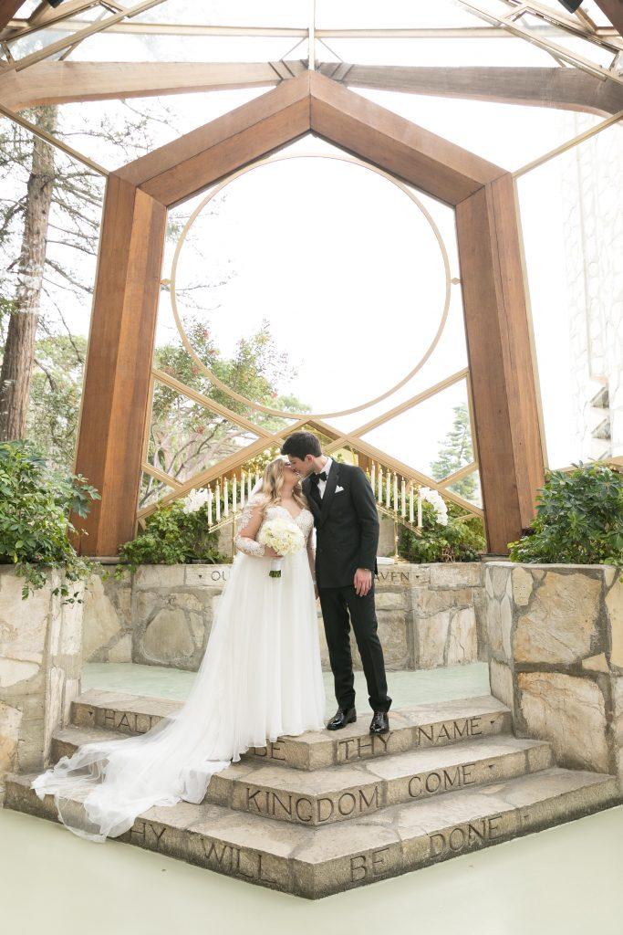 bride and groom kiss in wayfarers chapel glass church