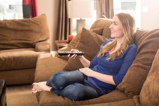 woman sitting on a couch with a remote watching tv when your pilots away