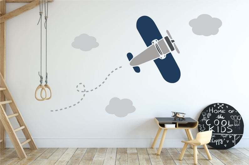 One large blue and grey airplane decals with grey clouds on a white wall