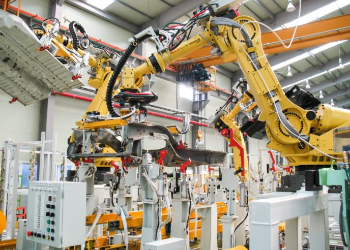 Two yellow Fanuc robots are moving pieces of metal in an automation cell.