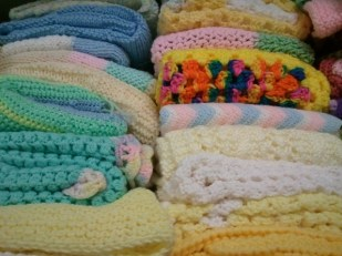 Lovely donors make shelves and shelves of handmade quilts and blankets.