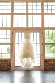 The Wedding Dress hanging by window at the Red Barn Events in Aubrey Texas
