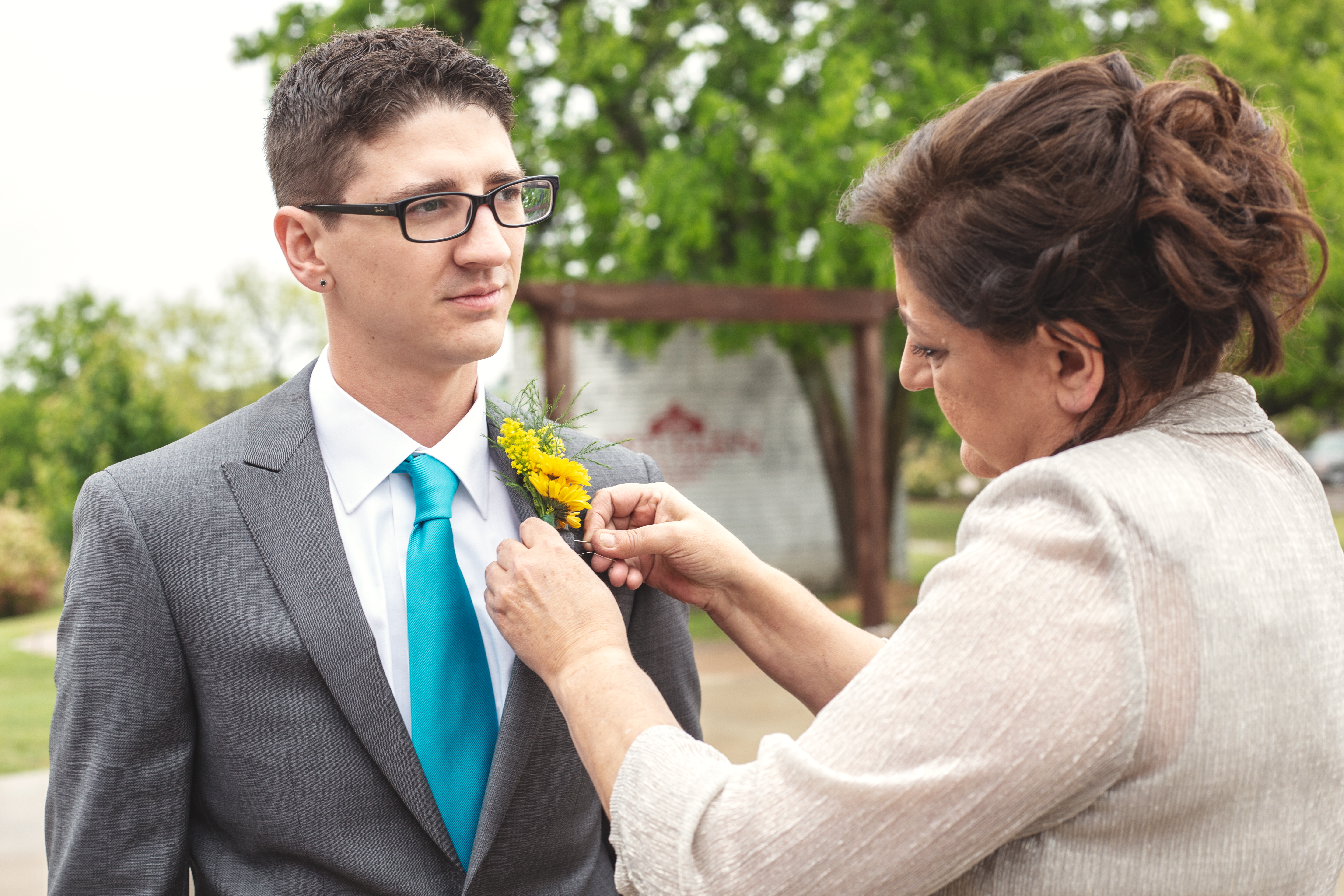 Mother helping groom with yellow boutonniere at the Red Barn Events | Taken by Skys the Limit Production