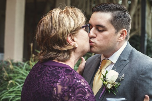 Groom and his mother giving each other a kiss before he says I do.