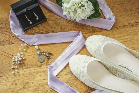 Detail shot of the Bride's earrings, shoes, flowers, purple robe, hair piece and something sentimental.