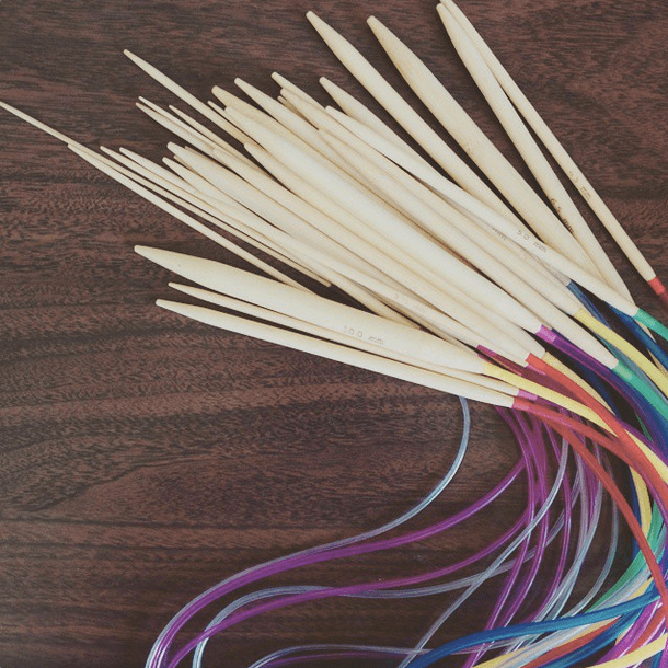 set of wooden knitting needles with multicoloured cords