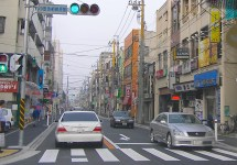 Most of the streets in Japan are much narrower than those in the U.S. or even Europe. This street is actually one of the more spacious streets. Note that this photo shows three lanes (two way traffic plus a turn lane), not just two lanes. Note all of the power lines and signs that make the road almost a visual stimulation overload.